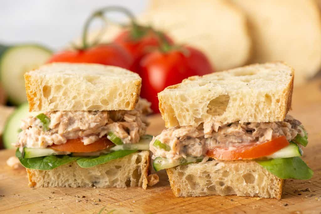 A Salmon Salad Sandwich on sliced ciabatta bread sliced in half on a cutting board.
