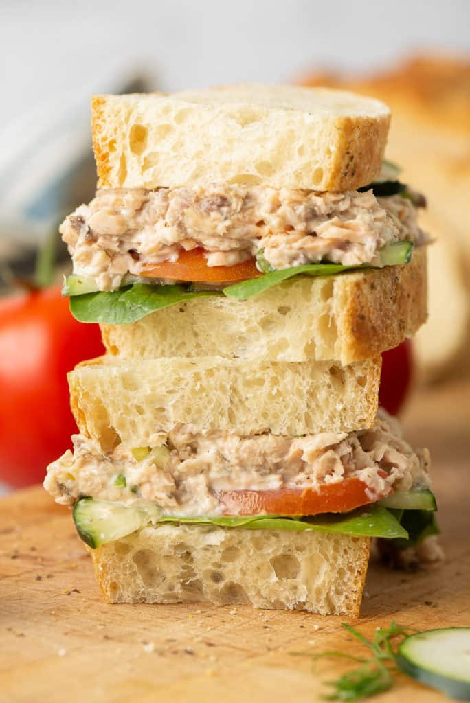 A Salmon Salad Sandwich with tomatoes and cucumber sliced in half and stacked.