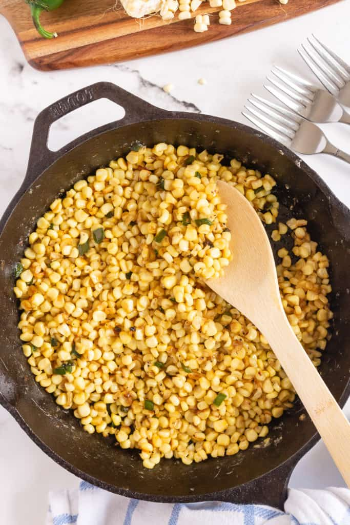 Corn being stirred with a wooden spoon in a cast iron skillet.