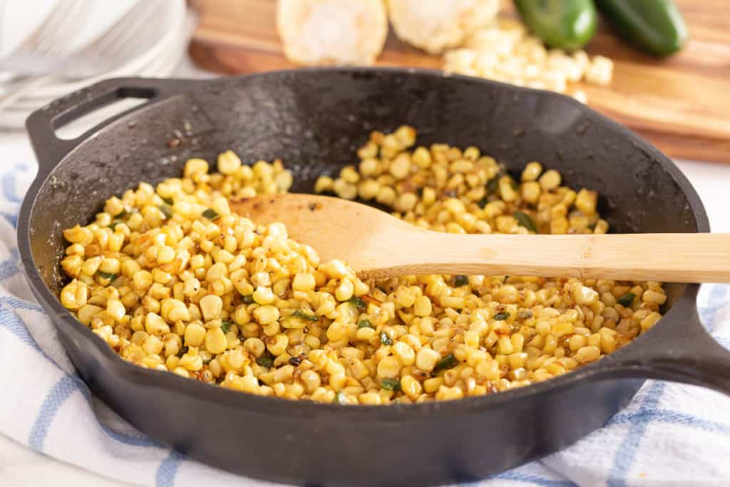 A wooden spoon stirring corn.