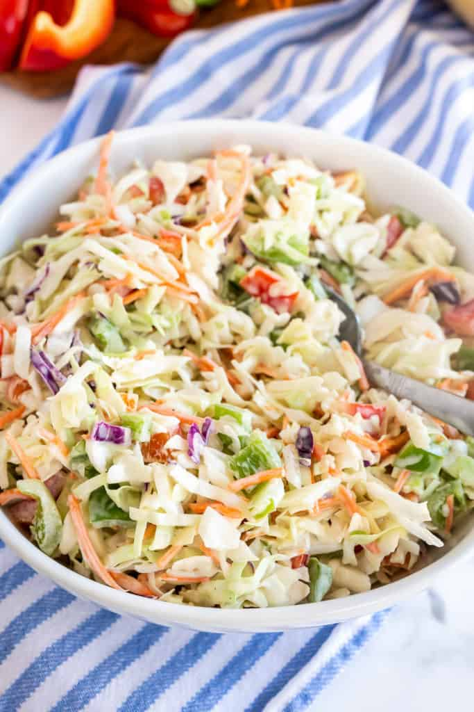 A white bowl filled with coleslaw with a spoon.
