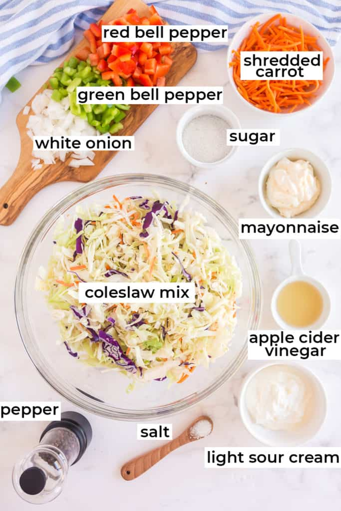 Coleslaw mix, bell peppers, onions and all the ingredients on a white surface.