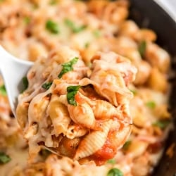 A spoon scoops Chicken Parmesan Pasta from a skillet.