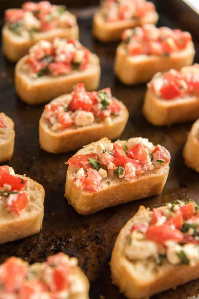 Baguette slices on a cookie sheet topped with tomatoes and feta.