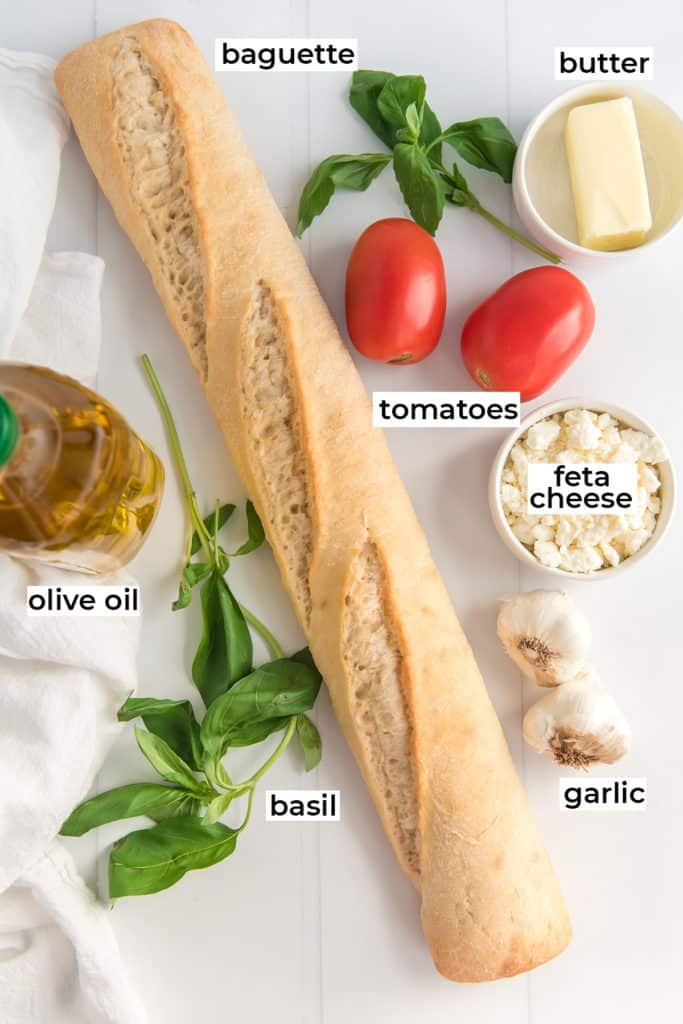 A baguette, tomatoes and other ingredients on a white surface with text overlay.