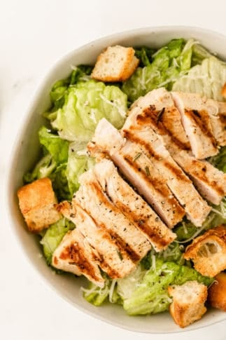 Salad topped with grilled chicken and focaccia croutons in a bowl.