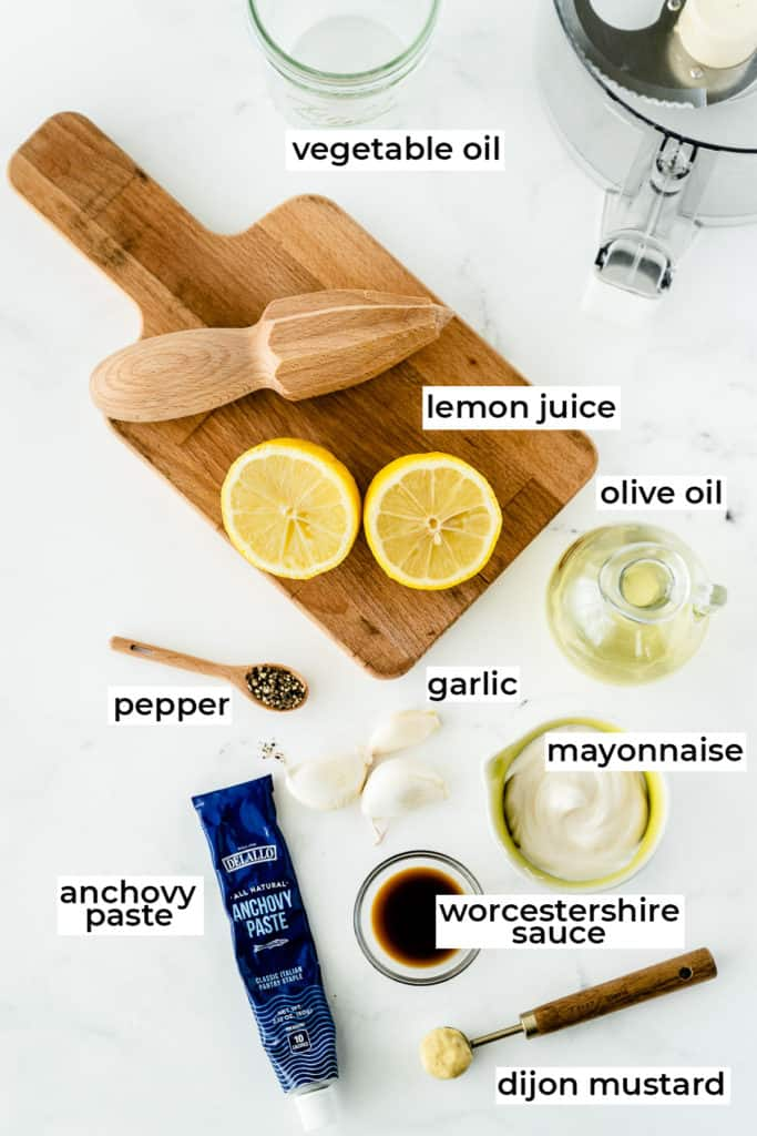 All the ingredients for Caesar Salad Dressing on a white surface.