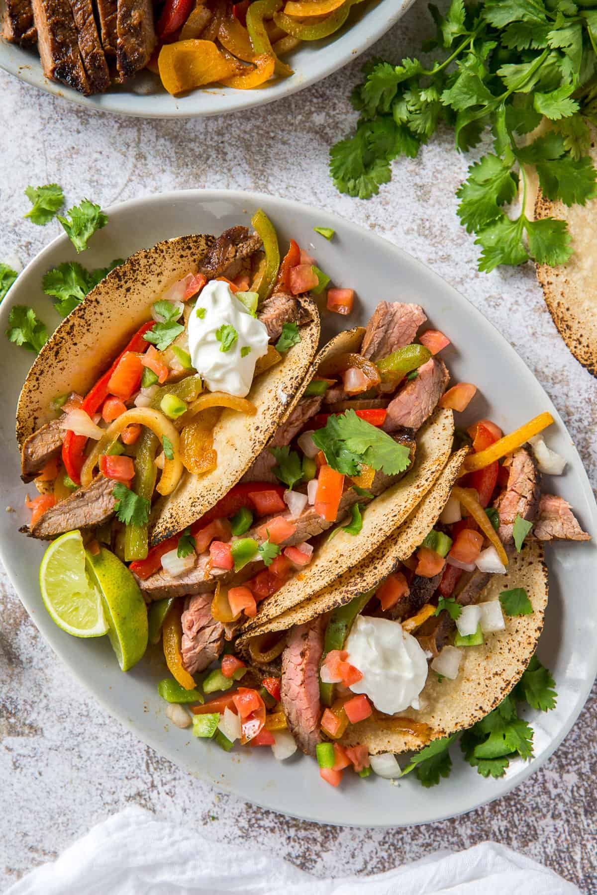 A platter full of tortillas stuffed with steak and vegetables.