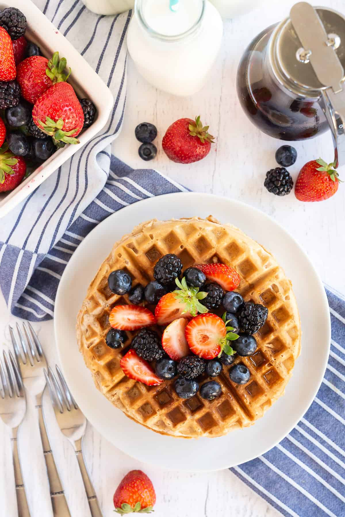 A top down shot of a stack of waffles on a white plate topped with fresh berries.