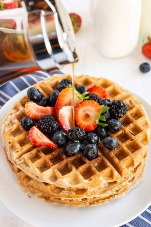 Maple syrup pours down on to a stack of waffles with fresh berries.