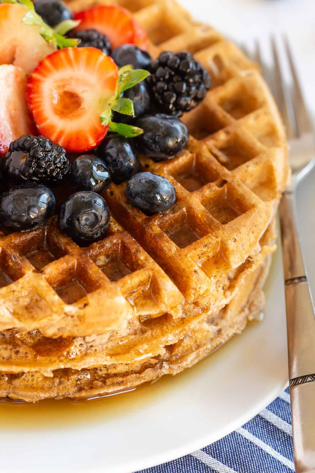A closeup of a stack of waffles topped with fresh berries.