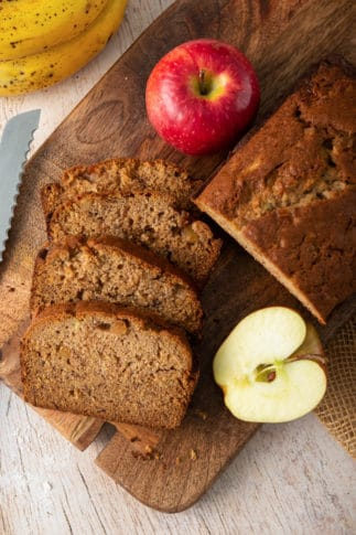 Slices of Apple Banana Bread on a cutting board with apples.