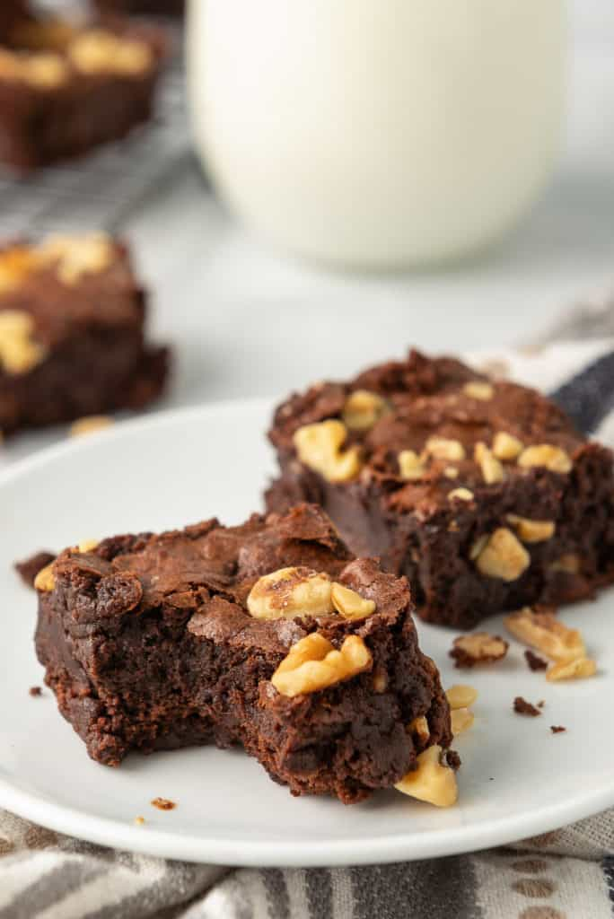 Two brownies on a plate, one with a bite missing.