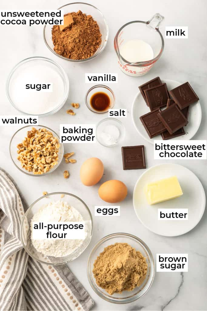 All the ingredients needed to make fudge brownies with walnuts on a white surface with text overlay.
