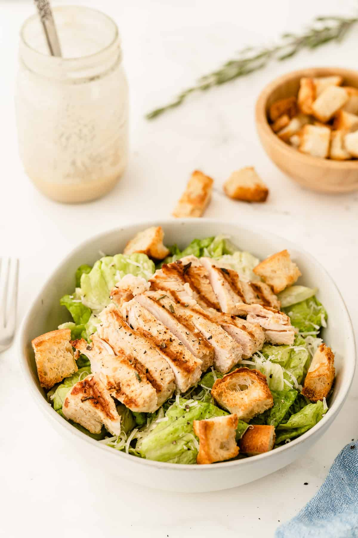 A bowl of chicken caesar salad with dressing in the background.