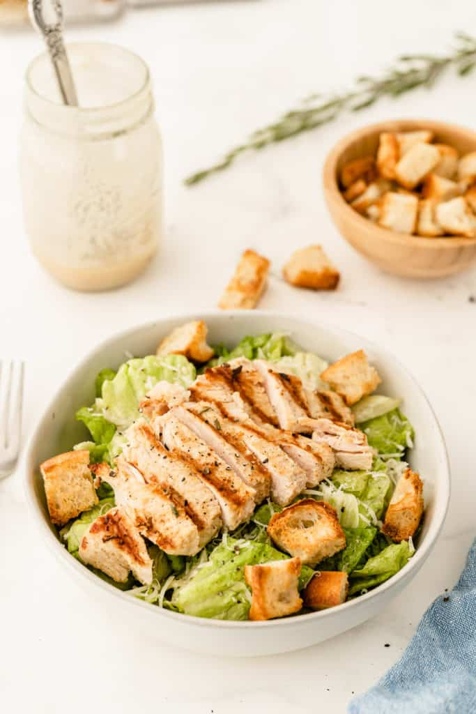 a salad topped with chicken with a mason jar filled with dressing.