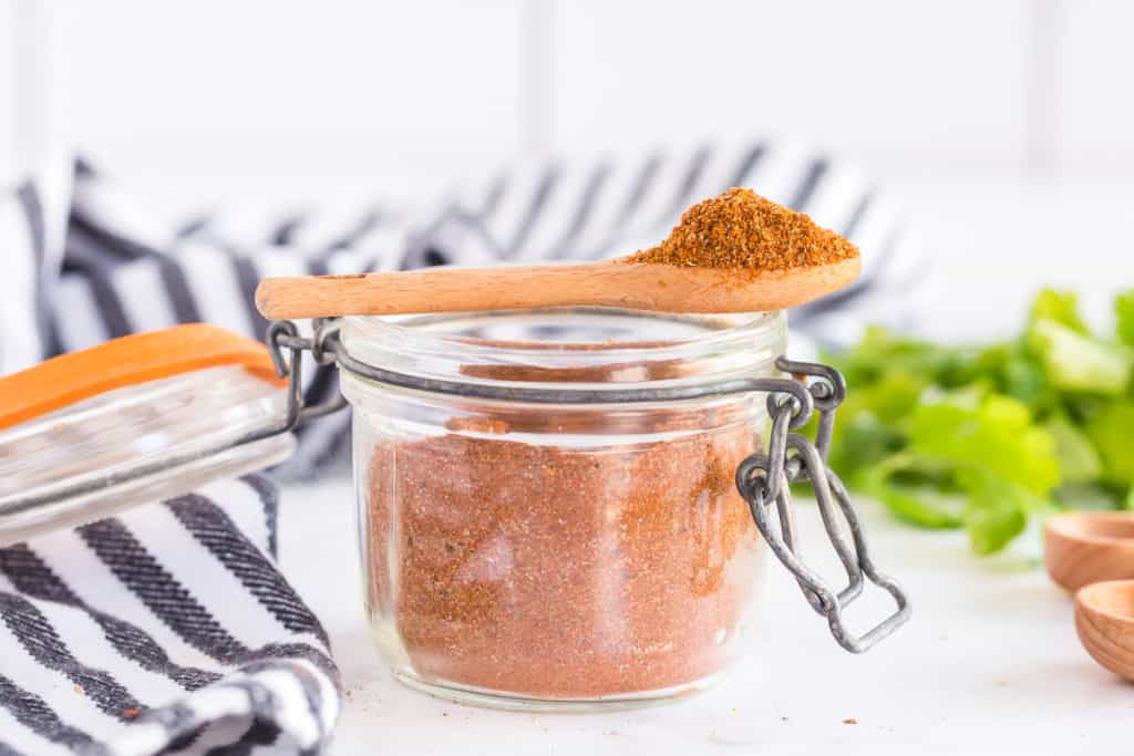 A spoon rests on top of a jar of seasoning.