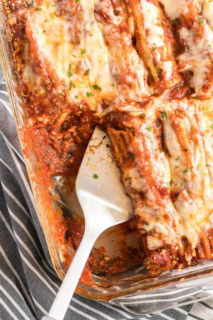 A spatula scoops manicotti from a baking dish.