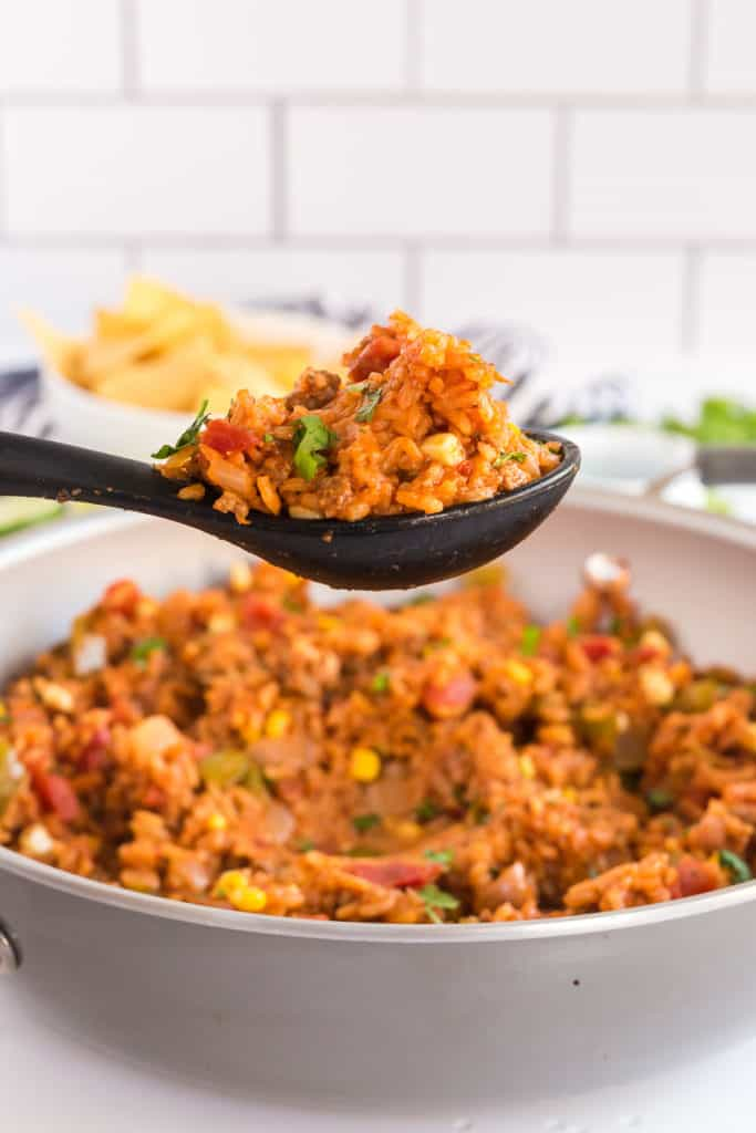 A spoon scoops Spanish Rice from a skillet.