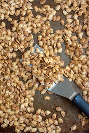 A spatula and baking sheet covered with roasted pumpkin seeds.