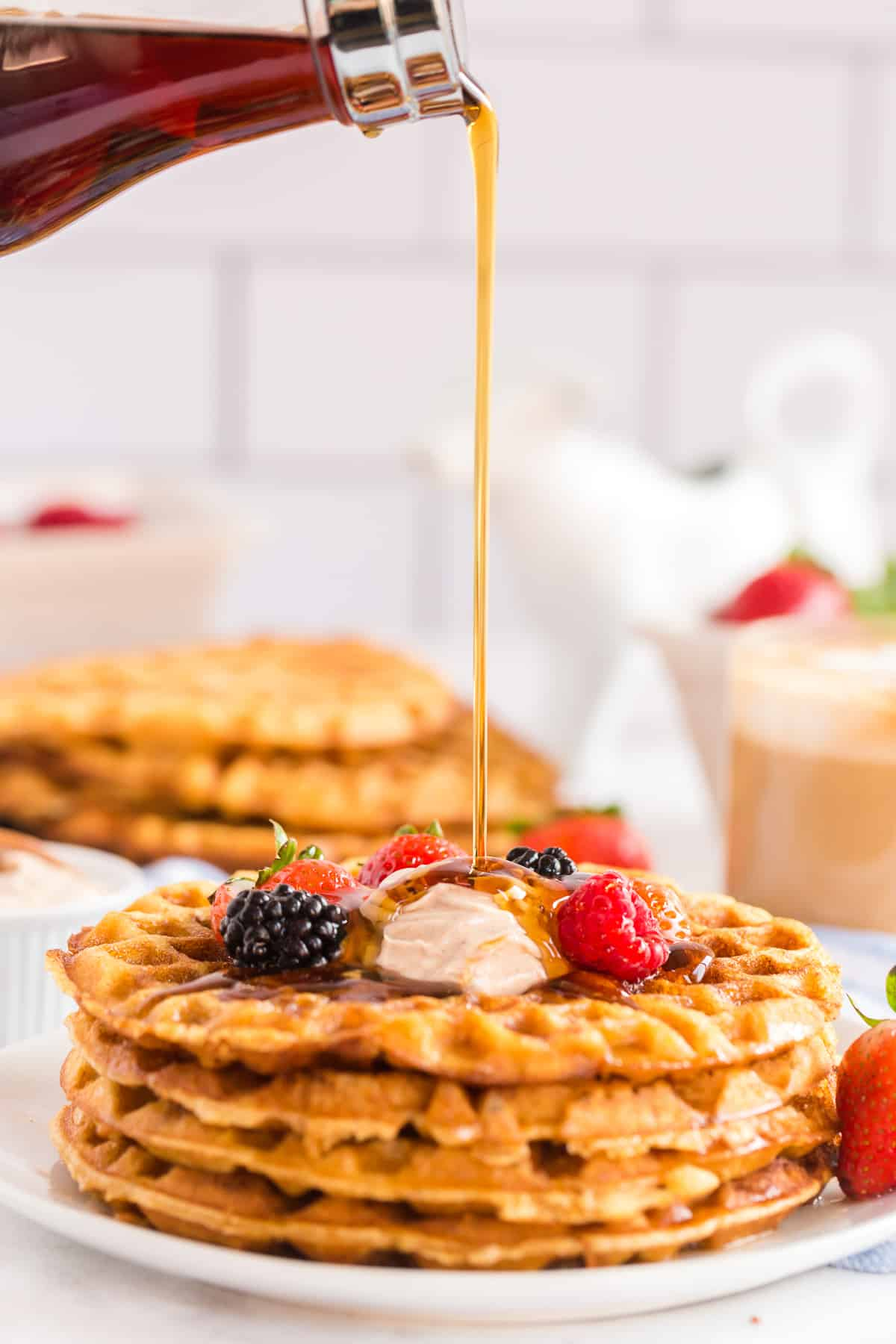 Maple syrup pouring on to a stack of sweet cornbread waffles.