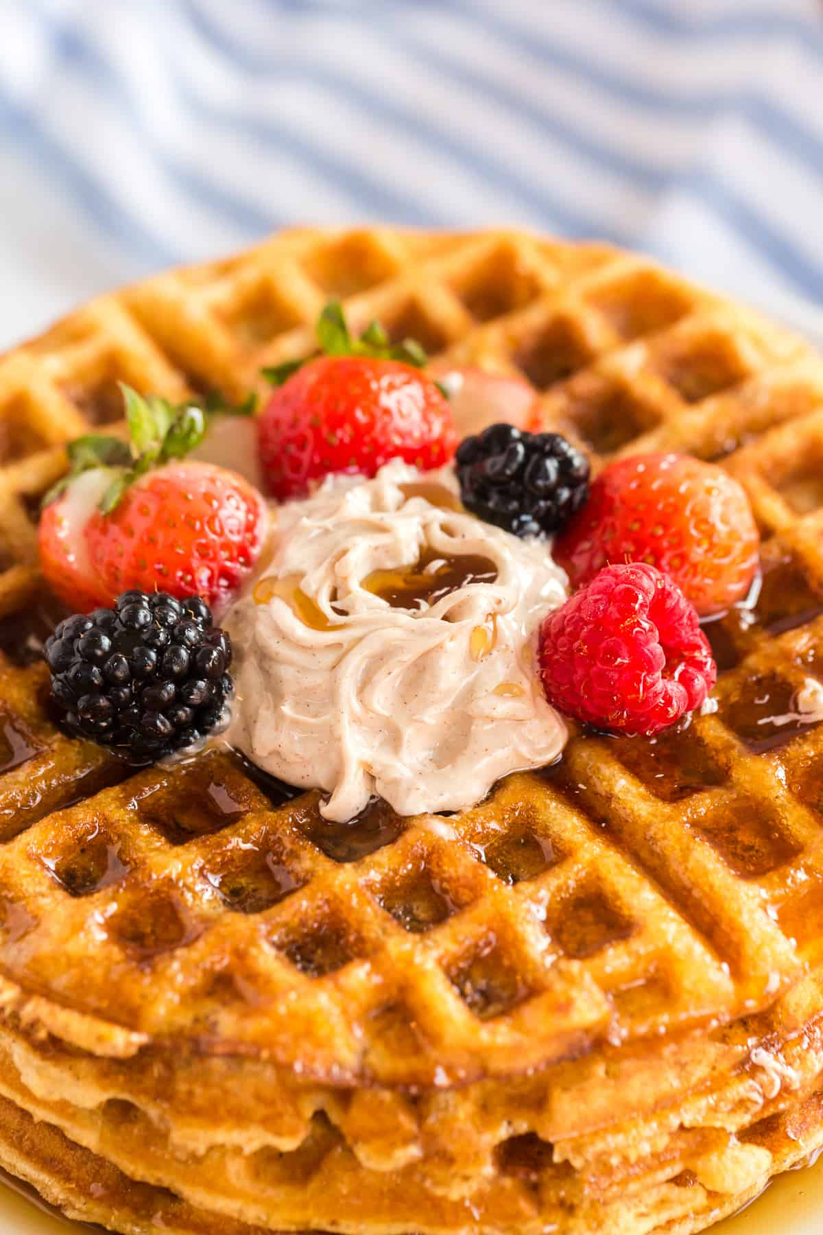 A closeup of a stack of cornbread waffles with berries and butter on top.