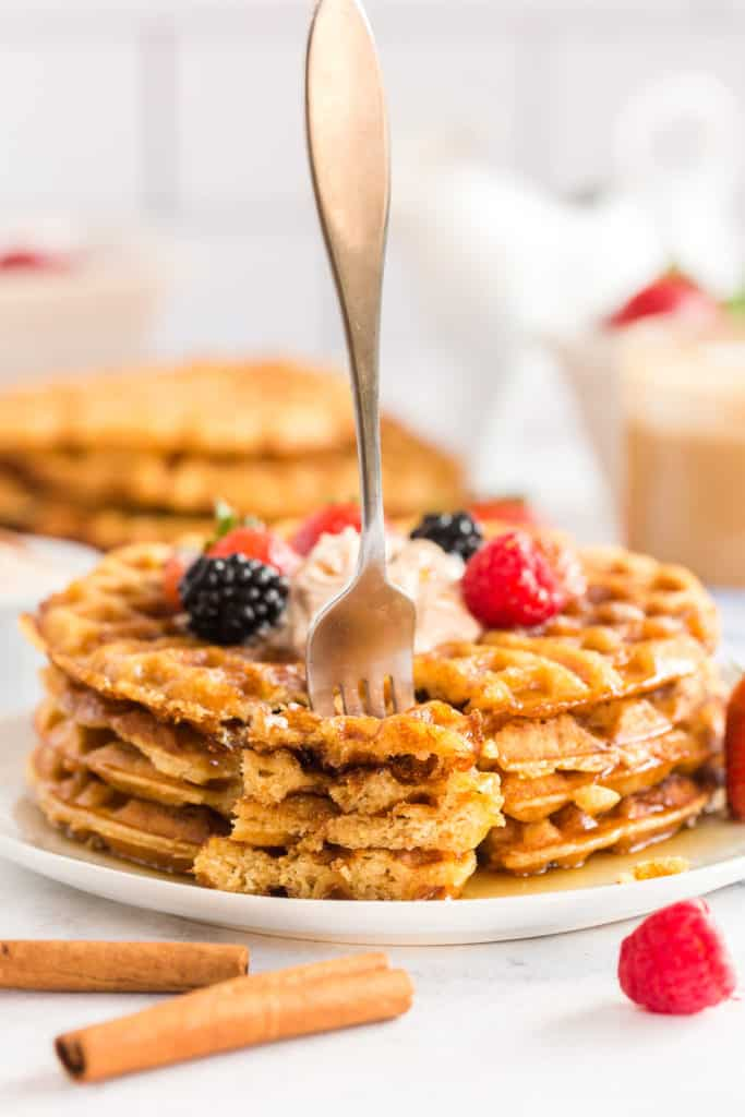 A fork stands upright stuck in pieces of sweet cornbread waffles on a plate.