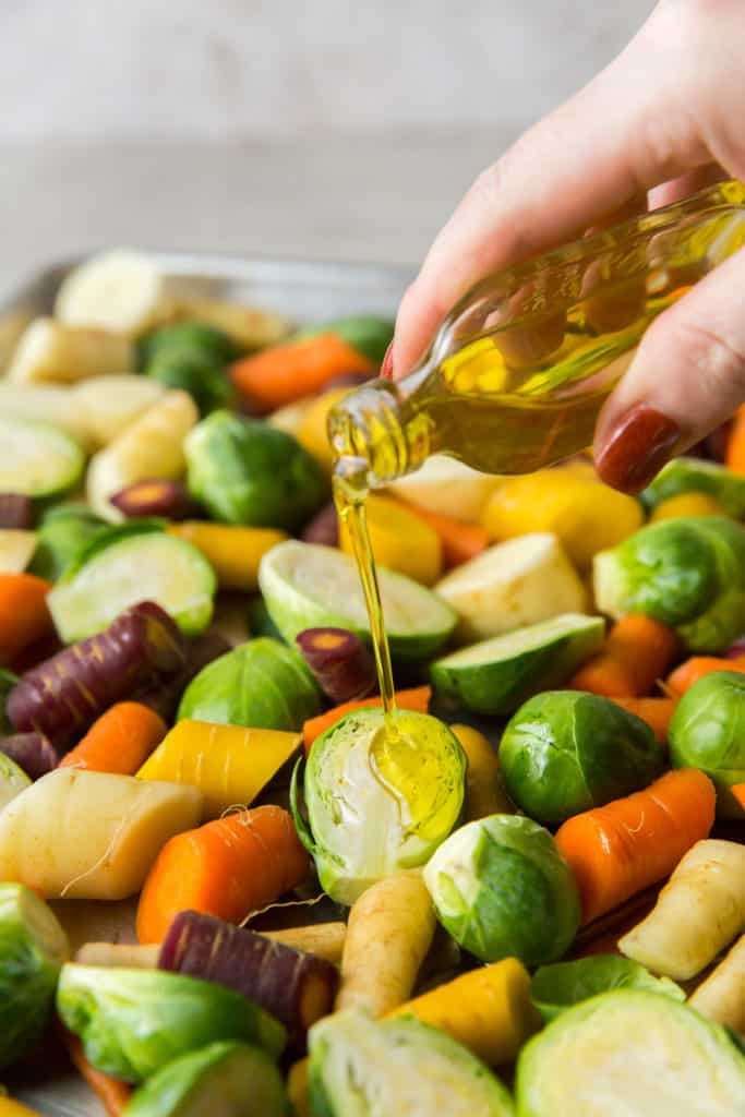 Oil is poured on to vegetables on a baking sheet.