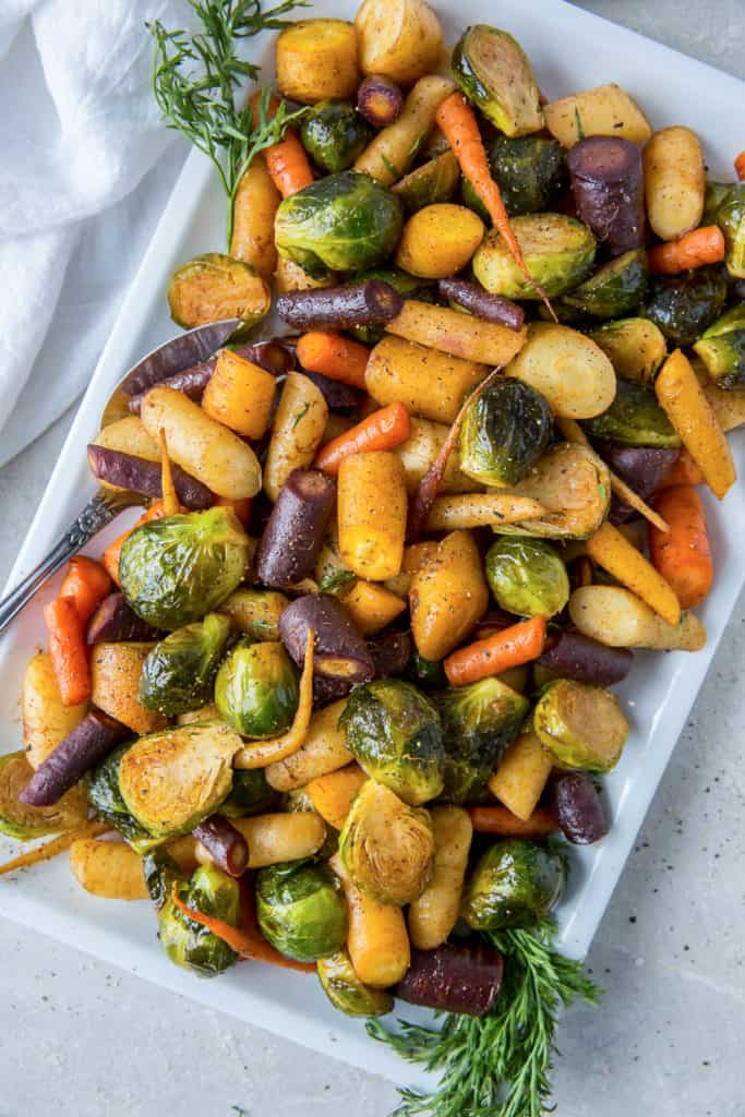 Roasted rainbow carrots and Brussels sprouts on a white platter.