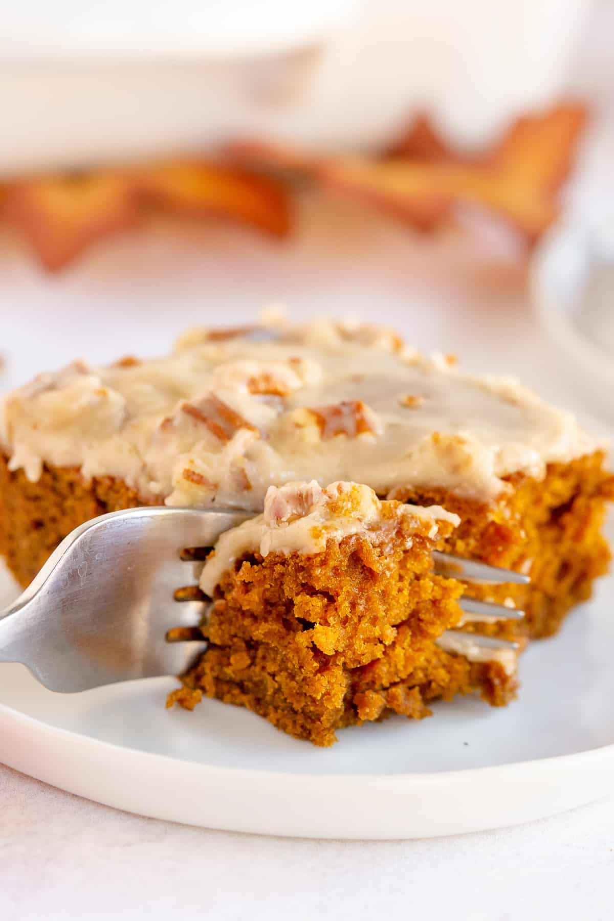 A fork breaks into a slice of pumpkin gingerbread on a plate.