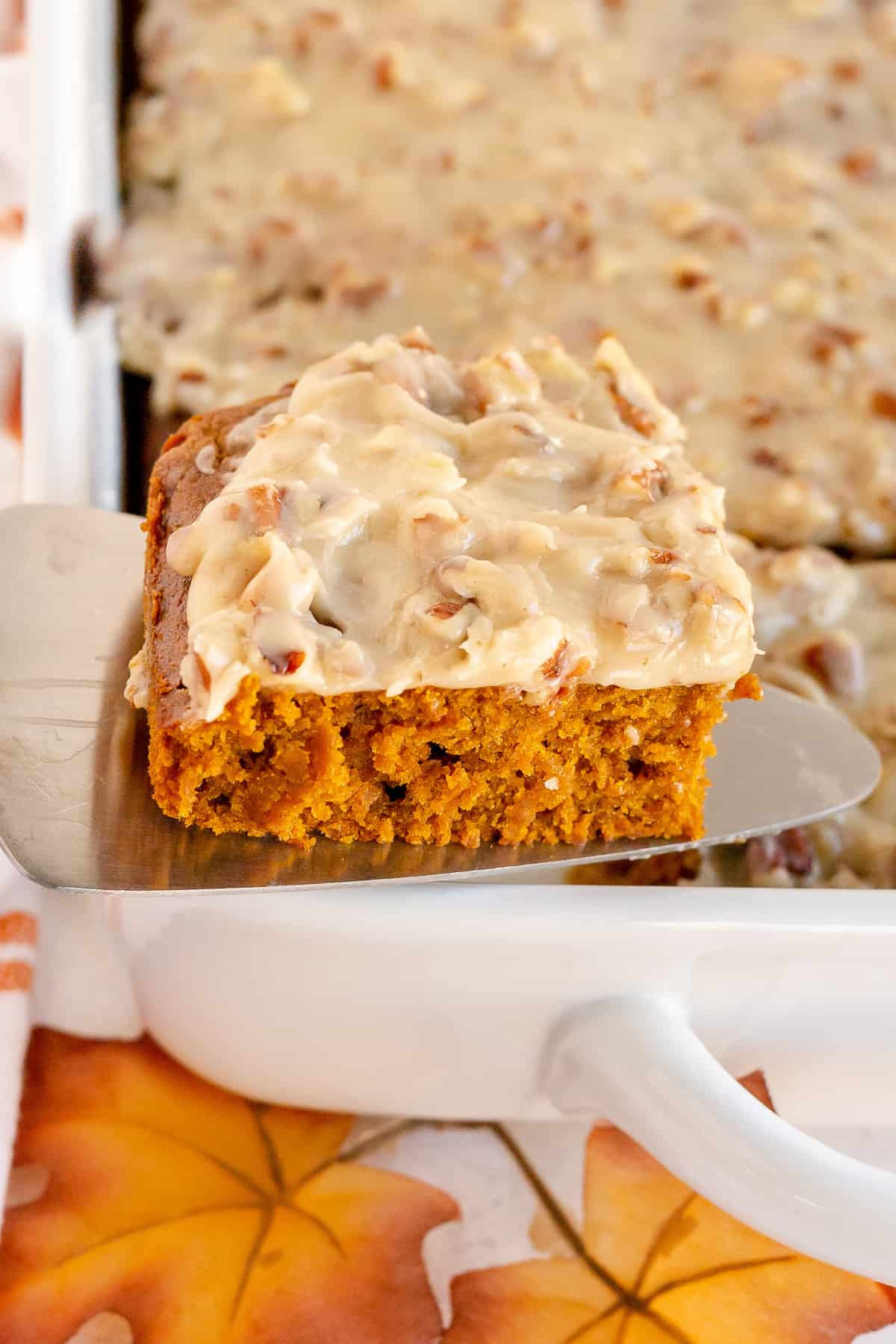 A spatula lifts a slice of pumpkin gingerbread from a baking dish.