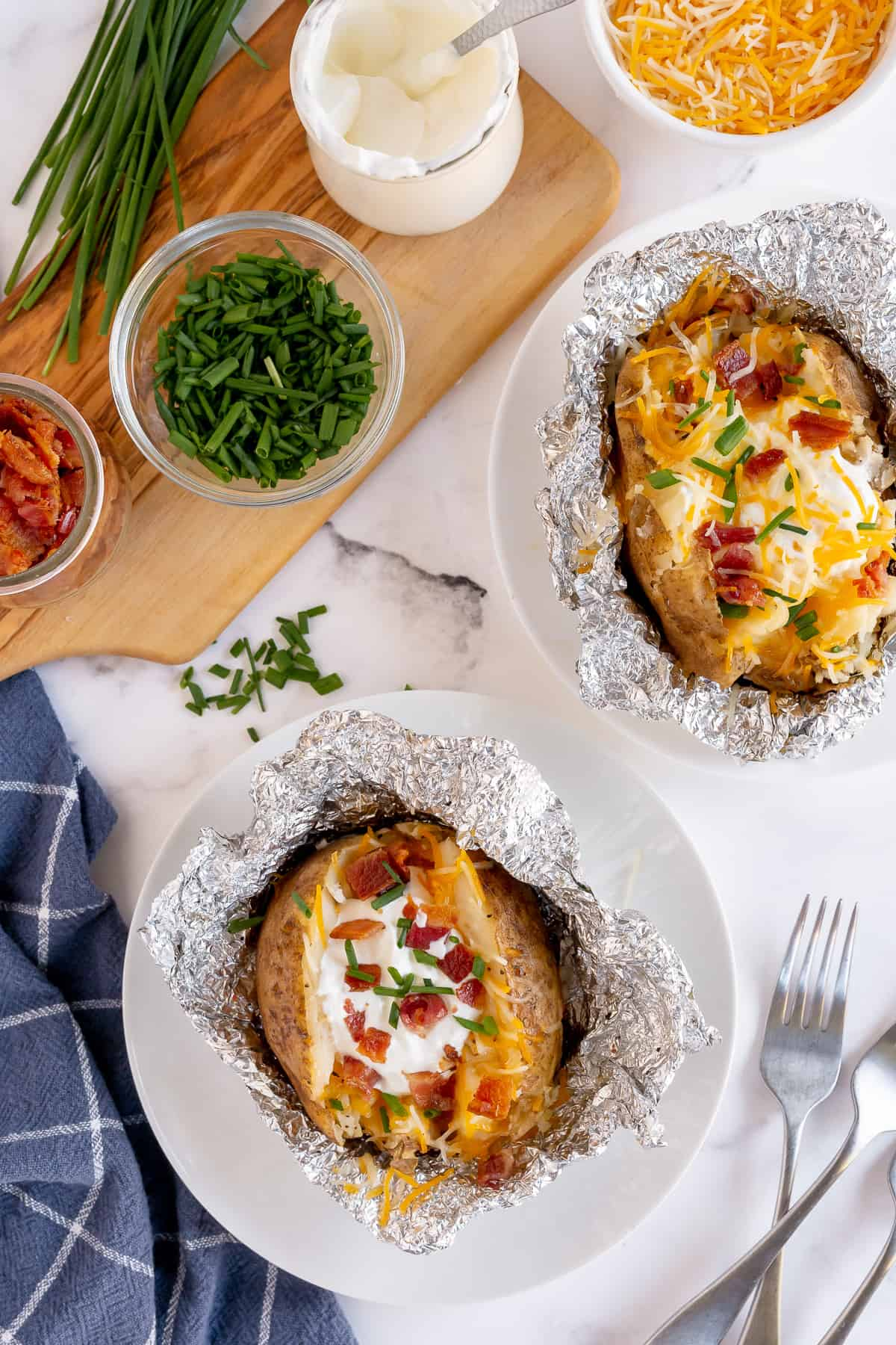 Two baked potatoes with toppings on plates.