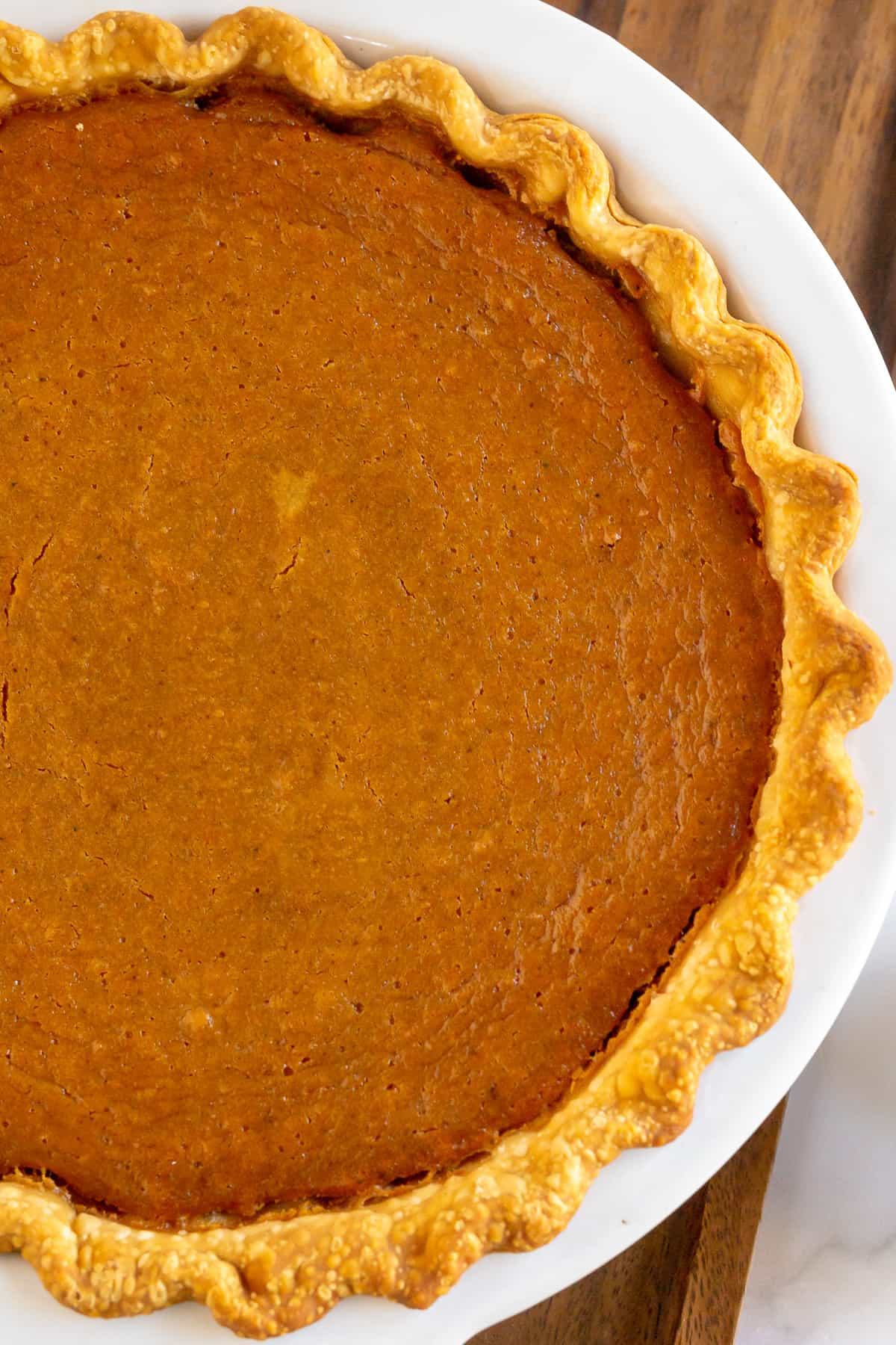 A close up of a sweet potato pie in a pie dish.