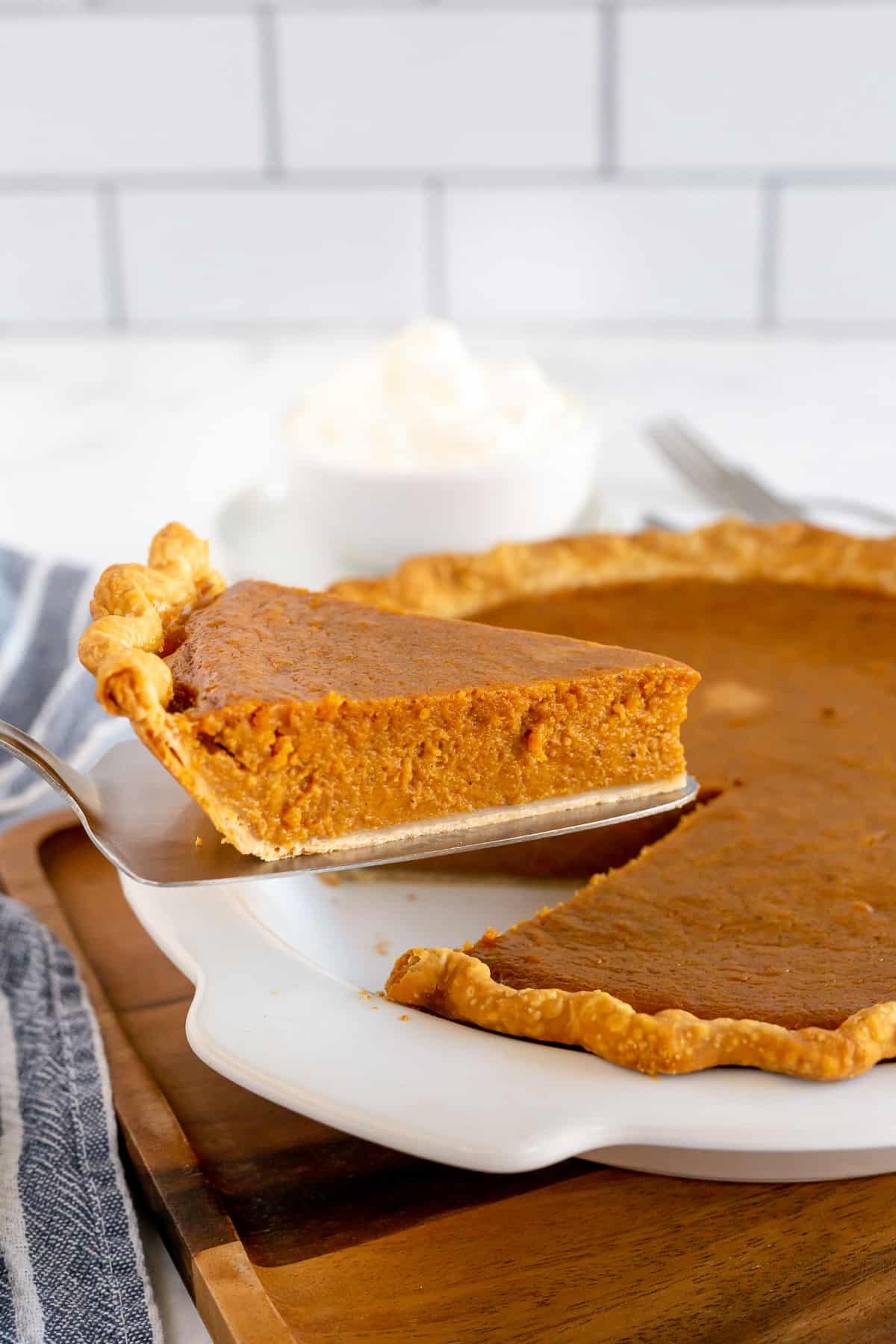 A spatula lifts a slice of pie from a pie dish.