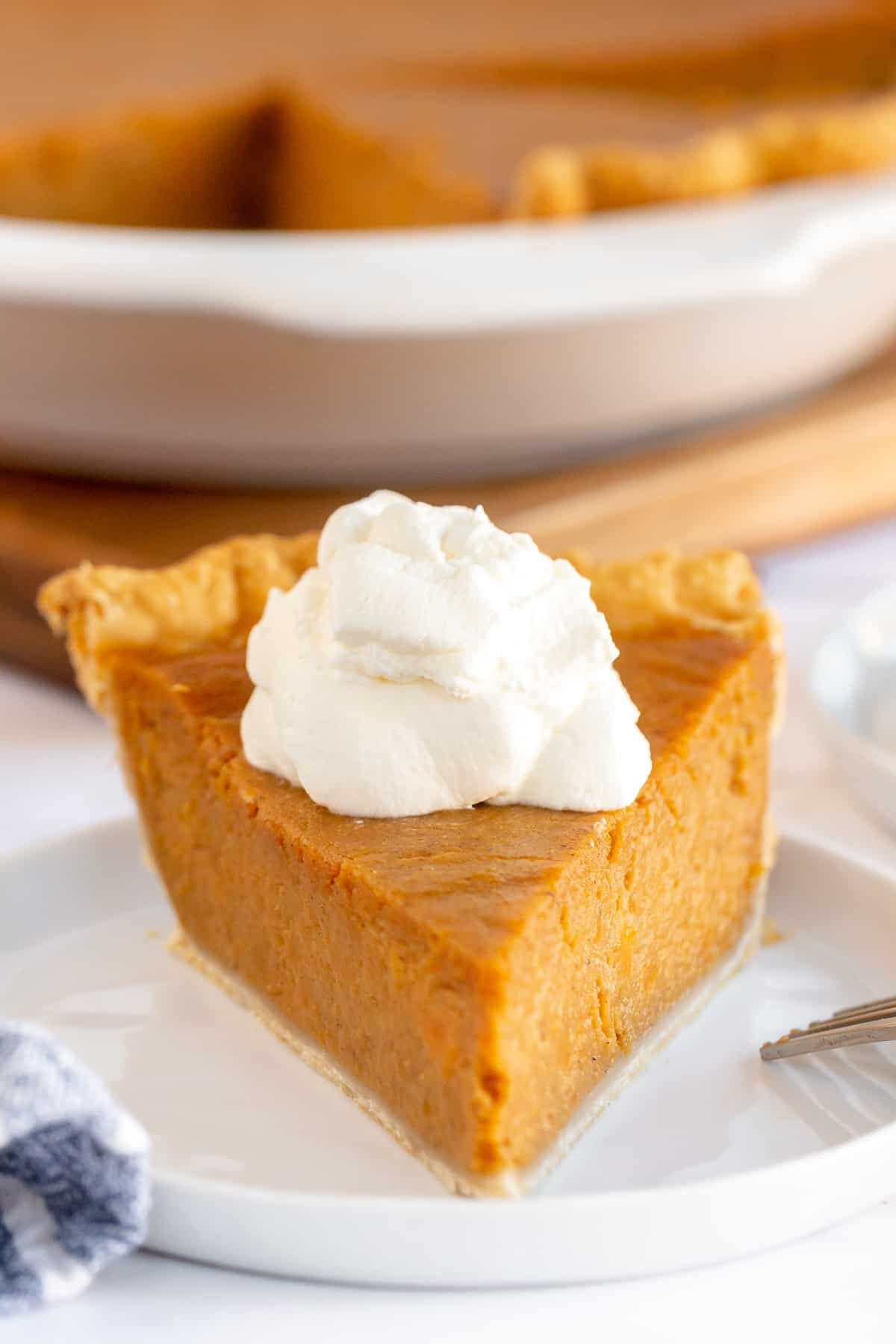 A slice of sweet potato pie toped with whipped cream.