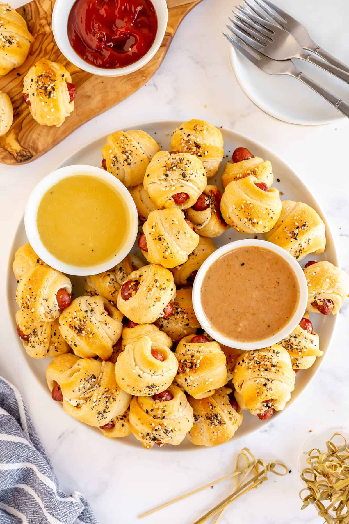 A platter of pigs in a blanket with everything bagel seasoning and dipping sauces.