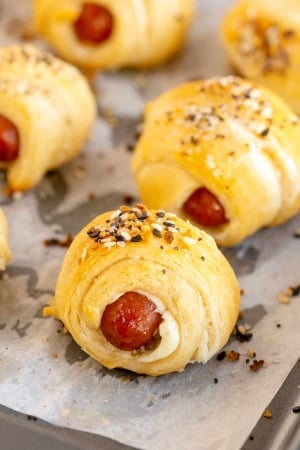 A close up of a pig in a blanket topped with everything bagel seasoning on a baking sheet.