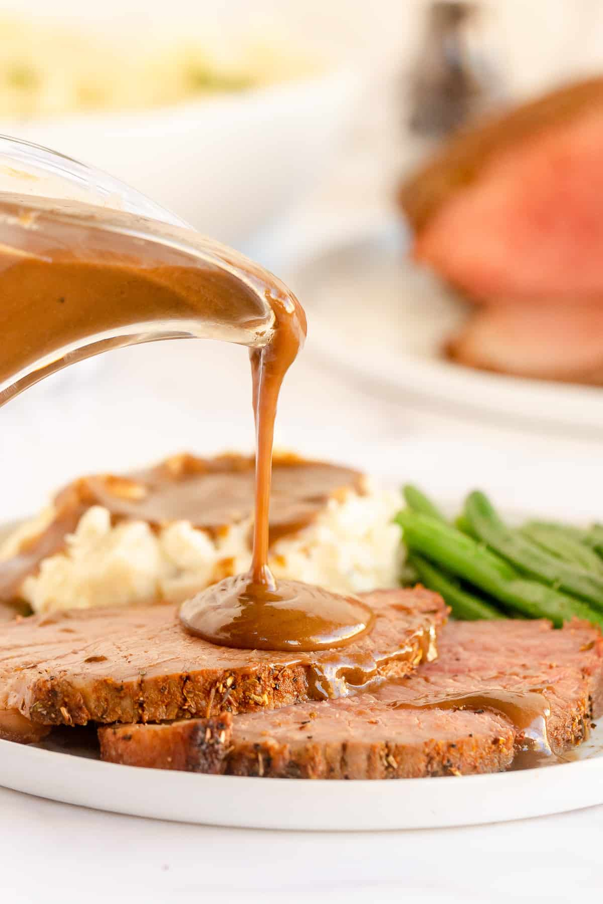 Gravy pouring on to slices of roast beef.