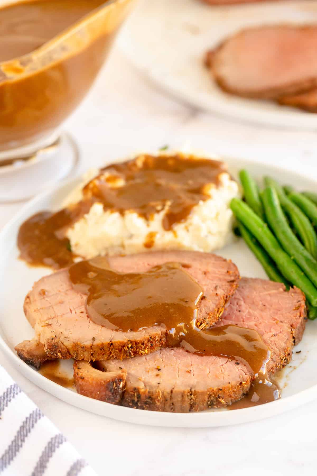 Slices of roast beef and mashed potatoes topped with gravy.
