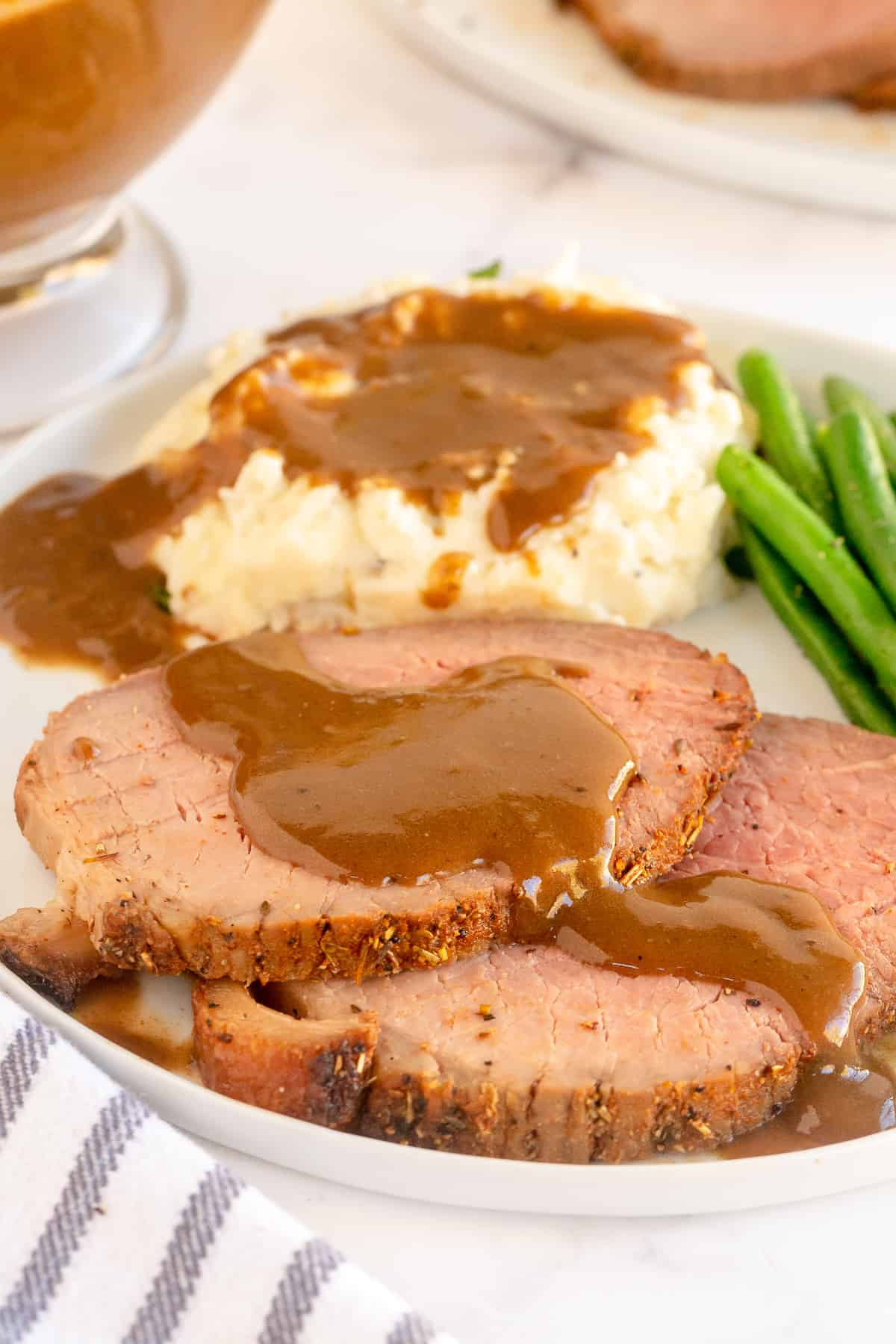 Slices of roast beef with gravy and mashed potatoes on a plate.
