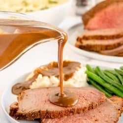 Gravy pours on to slices of roast beef.