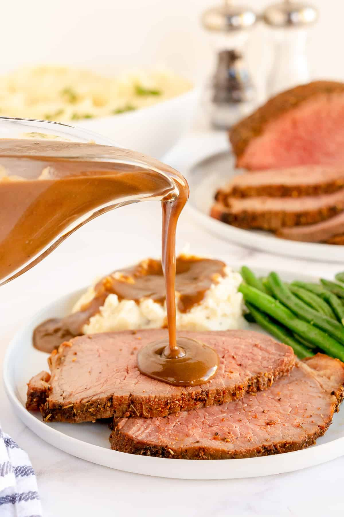 Gravy pours on to slices of eye of round roast beef.