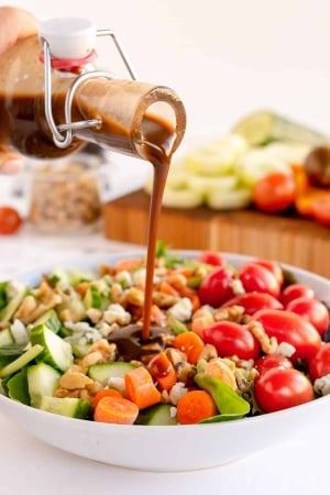 Vinaigrette pouring on to a salad.