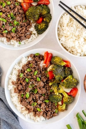 Bowls filled with rice, ground beef, and vegetables shot from over the top.
