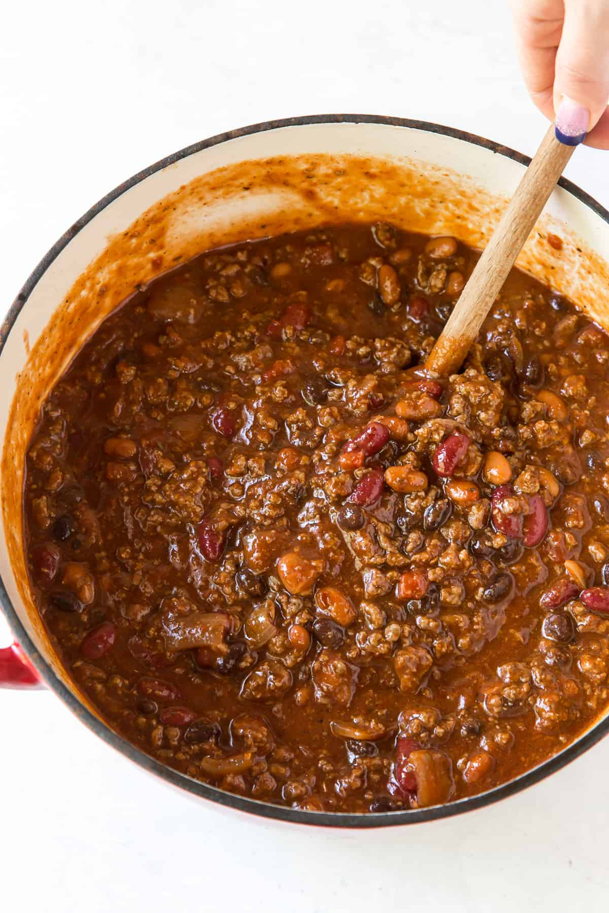A wooden spoon stirs a pot of Halftime Chili.