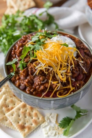 A bowl of chili topped with cheese and sour cream.