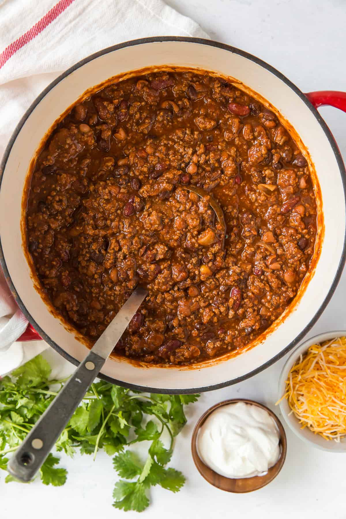 A ladle rests in a pot of chili with toppings set around it.