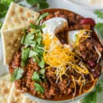 A bowl of beer chili with cheese, sour cream, and saltine crackers.