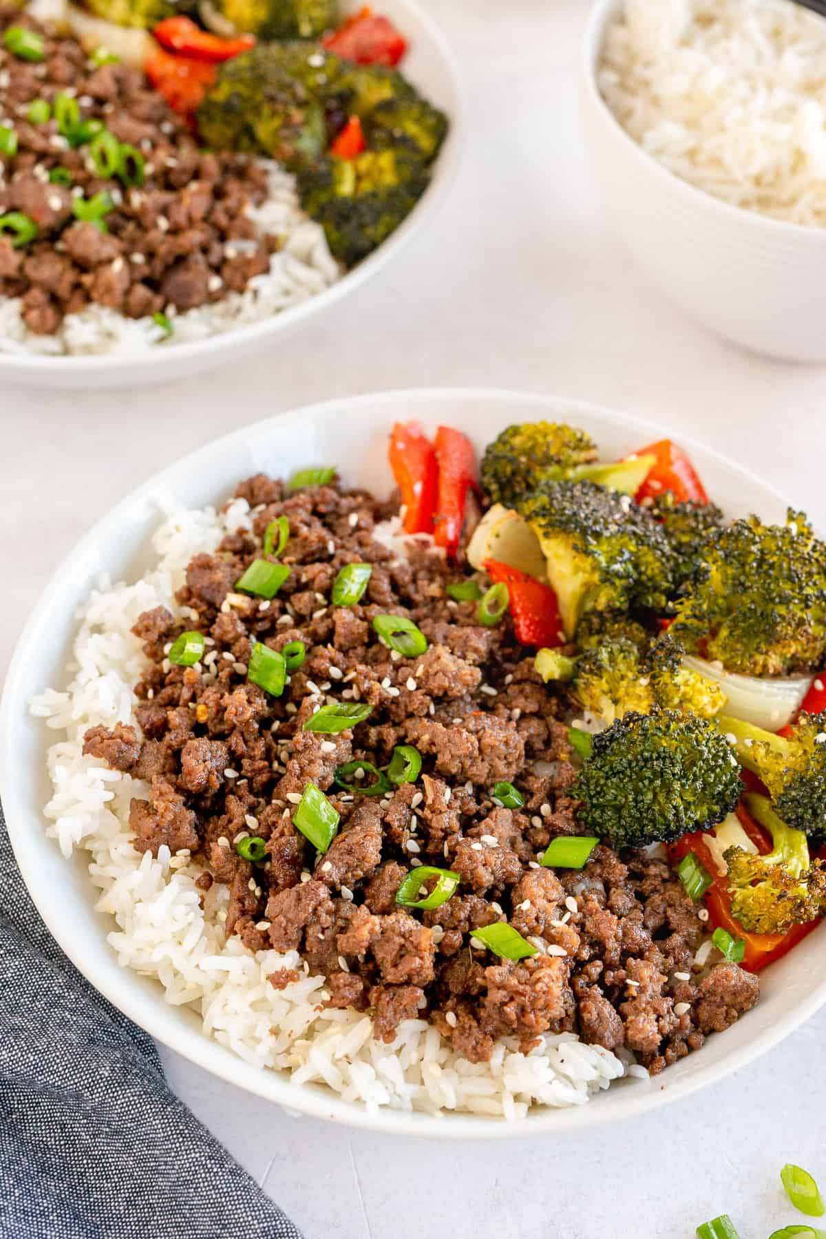 Korean beef o top of rice with vegetables in a white bowl.