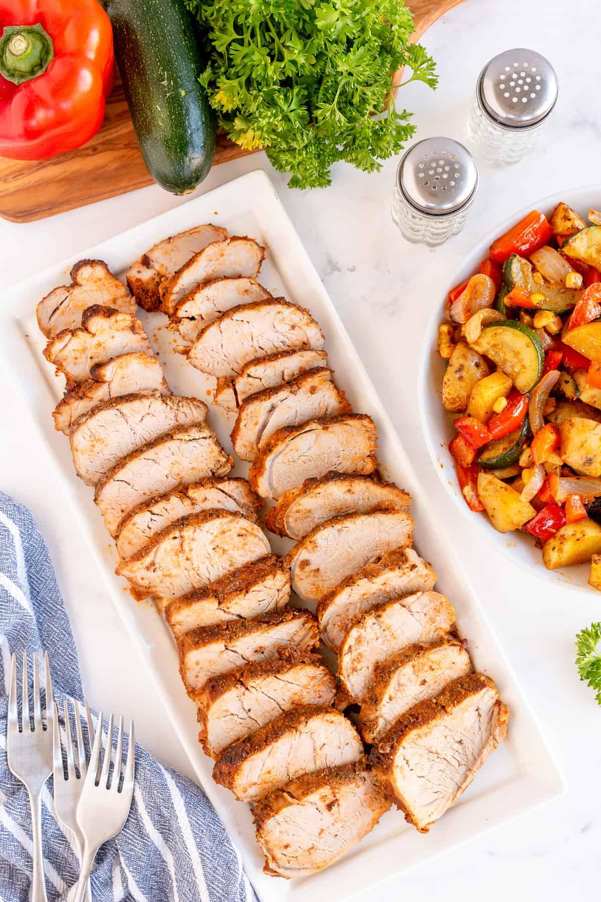 Sliced pork tenderloin on a serving platter next to a bowl of vegetables.